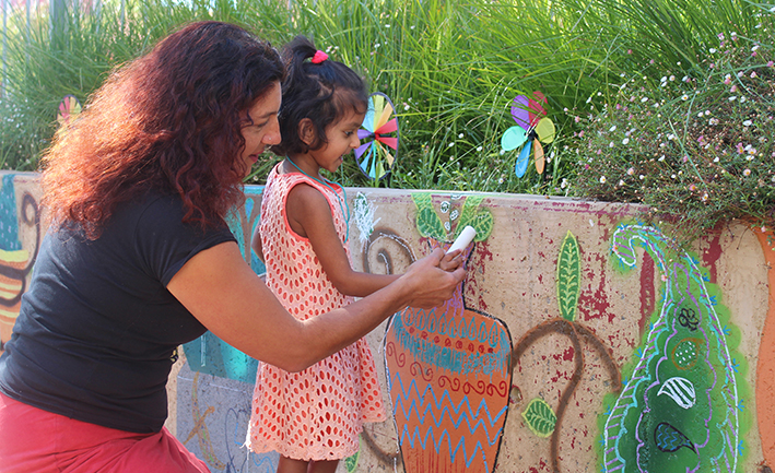 Teffany helping a small child to make her mark on a Tuggeranong wall to celebrate multiculturalism
